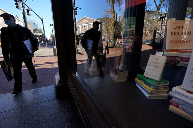 A man wears a mask while entering the Coop in Harvard Square, Thursday, Nov. 5, 2020. (AP Photo/Steven Senne)