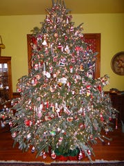 The centerpiece every year at the Engadine Inn & Cabins in Candler is a large, natural Christmas tree decorated with 3,000 lights and 1,200 Santa Claus ornaments. Co-owner Rick Bell is cautiously optimistic that the holiday season will be good for his inn and other local hospitality businesses.