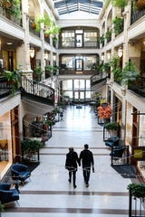 A couple walks through a quiet Grove Arcade, usually bustling with shoppers, November 17, 2020.
