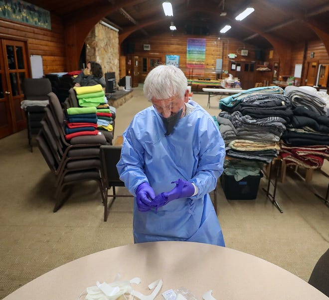 FILE — A volunteer at the Pilgrim Firs Camp in Port Orchard dons gloves and PPE on to deliver meals to those staying at the quarantine and isolation center in November.