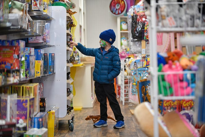 Nolan Resch, 6, of Hammonton, N.J., checks out Toy Market's dinosaur section while his mom Katie does some Christmas shopping on Wednesday, Nov. 18, 2020.