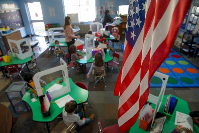 An American flag hangs from the top of a wall over the students studying at Norman Smith Elementary School in Clarksville, Tenn., on Monday, Nov. 16, 2020.