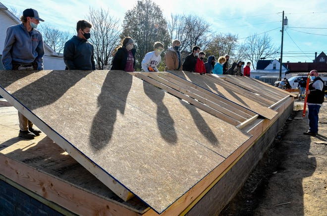 Instructor Kent Martins, right, watches as students from the Southern Indiana Career & Technical Center raise the first wall on a Habitat for Humanity home they are building in Evansville's Jacobsville neighborhood Thursday, November 19, 2020.