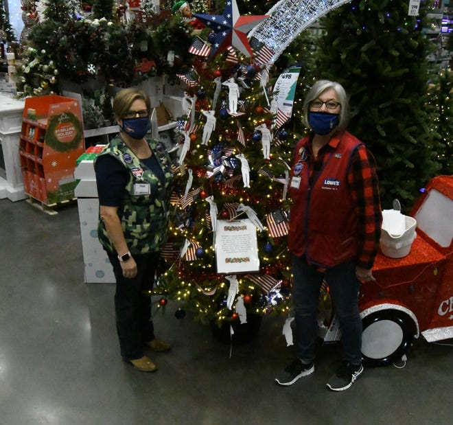 Mountain Home Lowe's employees Pam Burns and Debbie Miller stand next to the store's Veterans Tree.