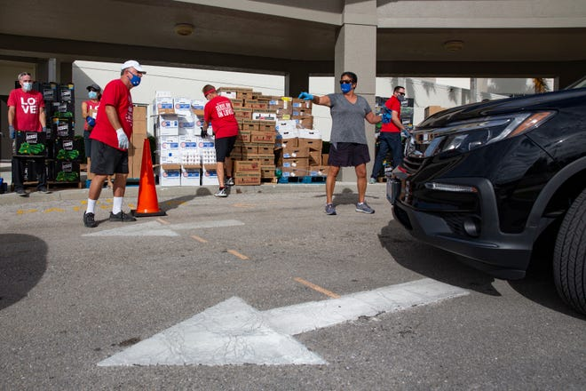 Volunteers guide vehicles in to a loading area as they get ready to pack the cars with Hope for the Holidays meal boxes, Thursday, Nov. 19, 2020, at the First Baptist Church of Naples.