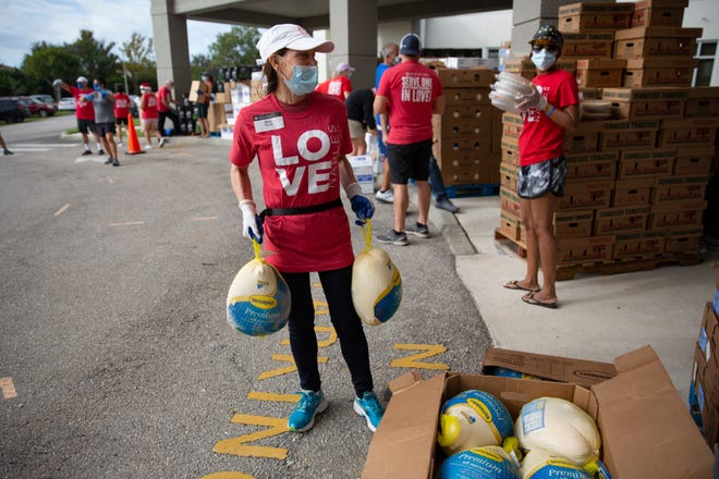 Volunteer Emily Paterakis prepares for the next wave of cars to arrive during the Hope for the Holidays meal distribution, Thursday, Nov. 19, 2020, at the First Baptist Church of Naples.