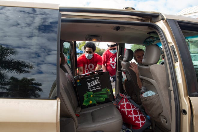 Volunteer Jordan Bunce, center, places a meal box in to a waiting car, Thursday, Nov. 19, 2020, at the First Baptist Church of Naples.