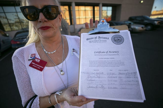 Janell Soyster Bucholdt, a member at large with the Maricopa County Republicans, holds the certificate of accuracy for a postelection logic and accuracy test with the tabulation machines at the Maricopa County elections tabulation center in Phoenix on Nov. 18, 2020. The Maricopa County Elections Department runs a logic and accuracy test with a number of sample ballots before and after every election. All of the ballots during the test were matched and accurate.