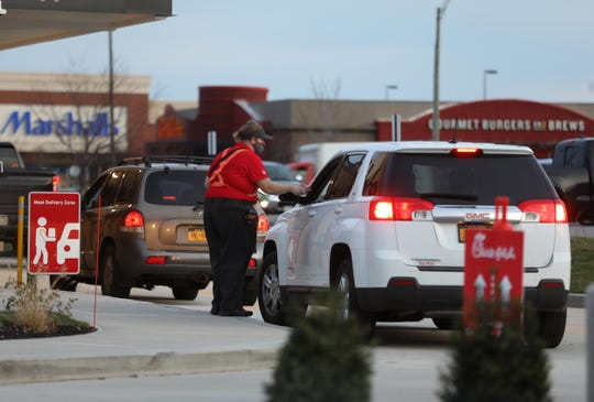 Chick-fil-A opened on Marketplace Drive November 19, 2020 in Henrietta.  Several cars went through the drive in around 7 a.m.  Employees come out to deliver orders and take payments on a mobile device.