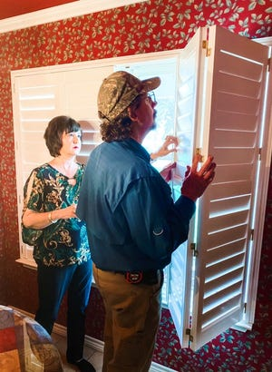 Janis Baucom and her husband Jim install shutters on a customer's window.
