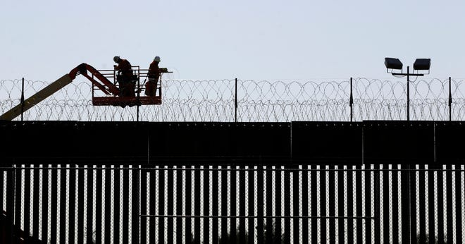 Workers line the top of the border fence between El Paso and Juarez with two layers of concertina wire Thursday, November, 19, 2020 near the Bridge of the Americas.