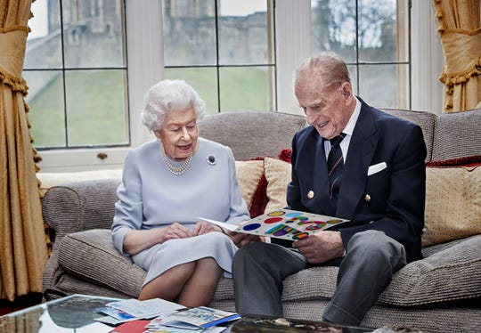 Queen Elizabeth II and Prince Philip, Duke of Edinburgh, look at 真人百家家乐官网网站homemade wedding anniversary card, given to them by their great grandchildren, at Windsor Castle ahead of their 73rd anniversary, Nov. 17, 2020.