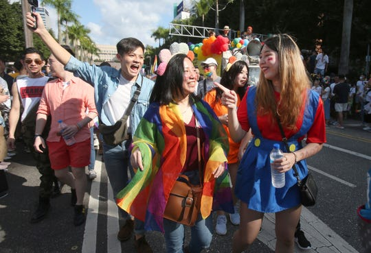 Participants march through the street during an LGBTQ pride parade in Taipei, Taiwan, Oct. 31, 2020. In the U.S., most pride events in June were canceled.