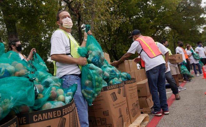 Wearing a face mask to prevent to spread of COVID-19, volunteer Scot Wingo grabs bags of food to distribute during a North Texas Food Bank drive-thru event on Oct. 22, 2020, in Dallas.