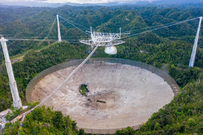 An aerial view shows a hole in the dish panels of the Arecibo Observatory in Arecibo, Puerto Rico, on November 19, 2020. The National Science Foundation announced it will decommission the radio telescope following two cable breaks in recent months which have brought the structure to near collapse.