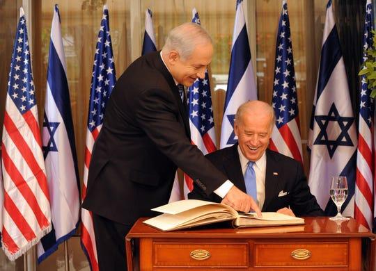 Israeli Prime Minister Benjamin Netanyahu helps US Vice President Joe Biden as he signs the guestbook at the Prime Minister's residence on March 9, 2010 in Jerusalem, Israel.