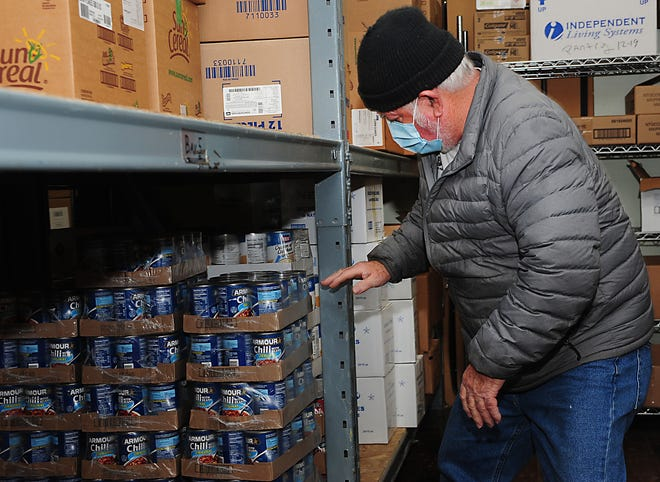 Ralph Stewart checks the inventory of cases of chili Wednesday at the Alliance Community Pantry.