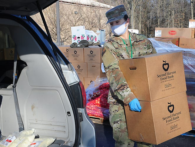 Alexis Seman of the Ohio Air National Guard loads boxes of food into a van Friday during a food distribution event sponsored by the Mahoning Valley Second Harvest Food Bank at B.L. Miller Elementary School.