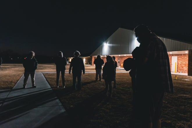 A group gathers behind Bartlesville Assisted Living on Thursday night for a prayer vigil for frontline workers at the facility during the COVID-19 pandemic.