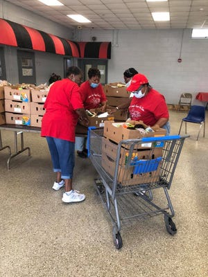 Jasper County Hunger Free Zone volunteers prepare boxes at the pantry for a recent food distribution. The group is in need of folding chairs and tables, a large refrigerator and freezer and food donations.
