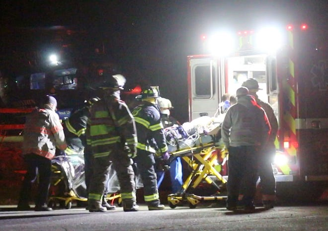 Rescuers load a patient into an ambulance near a recreation area under the Sagamore Bridge on Thursday night en route to a MedFlight landing area near the former Hoxie School. The patient had life-threatening injuries from a gunshot wound and was flown to Rhode Island Hospital. [David Curran photo]