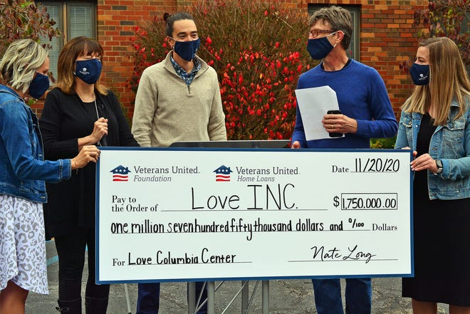 Veterans United Foundation Board President Erik Morse, third from left, helps present a $1.75 million check Friday to Love Inc. co-founders Jane Williams, second from left, and Pat McMurray, second from right. The gift will help Love Inc. purchase a new location on Walnut Street at the former home of Boone County Family Resources.