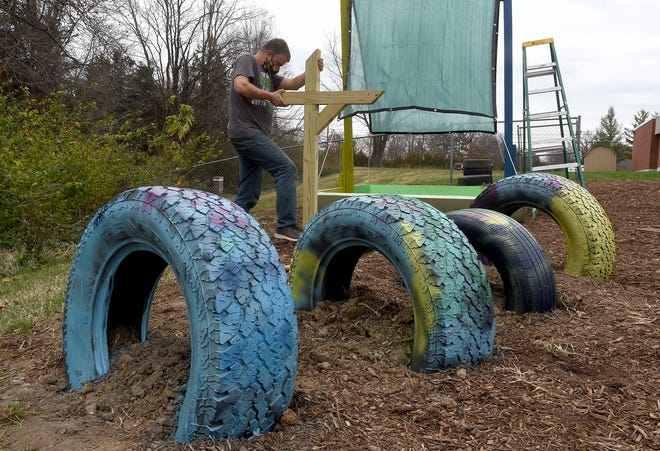 Columbia Public Schools Science Coordinator Mike Szydlowski works on new playground equipment at Midway Heights Elementary School on Friday. Szydlowski and volunteer work teams have been installing nature play areas at area schools that allow students to use their imaginations and to incorporate science and nature into their play.