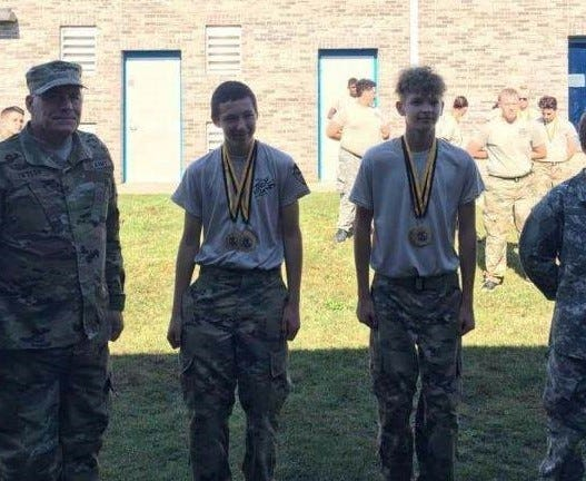 Washington County Superintendent Joe Taylor presents Cadets Trey Metzler and Trenton Simmons with the 1st place 3.2 mile Team Run medal and Freshman Male 2nd place medal.