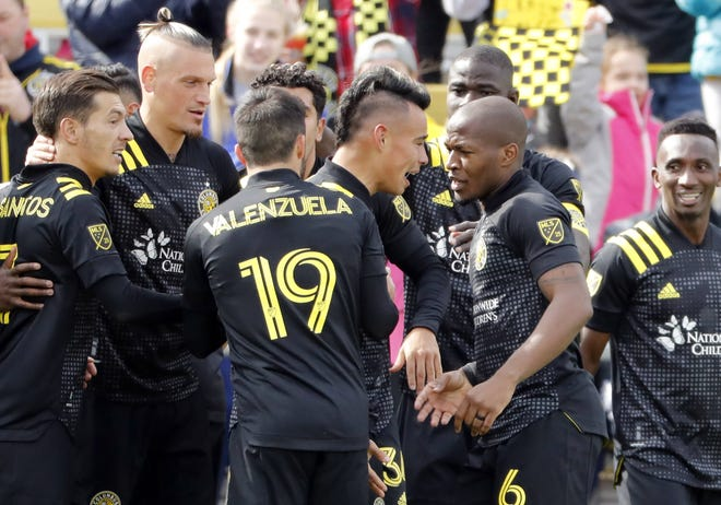 Lucas Zelarayan is mobbed by Crew teammates, including Darlington Nagbe (6), after scoring the only goal in a season-opening win over New York City at Mapfre Stadium.