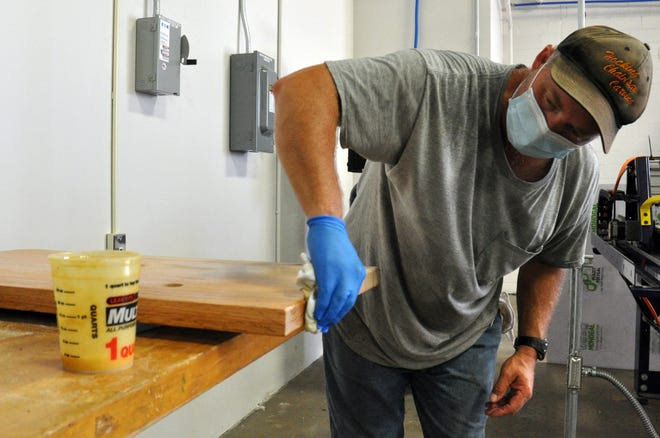 Dale Bockrath, a 1991 graduate of Hocking College, applies a finish to a countertop on Aug. 14, 2020, at the Hocking College Wood Lab in Nelsonville. Bockrath built bedframes vanity counter tops and other furniture for 43 rooms in The Lodge at Hocking College. The hotel is tentatively scheduled to open in January 2021.