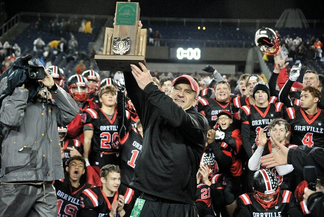 Doug Davault holds the Div. V state championship trophy after leading Orrville to the state title in 2018.