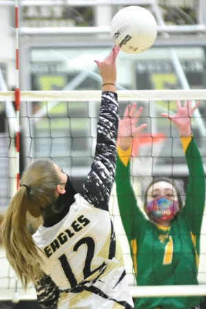 East Davidson's Callie Warrick (12) and West Davidson's Ana Tedder square off at the net Thursday night at East Davidson. [David Yemm for The Dispatch]