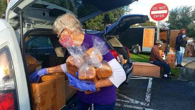 Susan Remington loads up on loaves of bread to give to people in need outside of the Wayne G. Sanborn Activity Center in DeLand on Thursday, Nov. 19, 2020. The drive-thru food pantry was put on by Backpack Buddies of Orange City, a nonprofit founded by Kelli Marks.