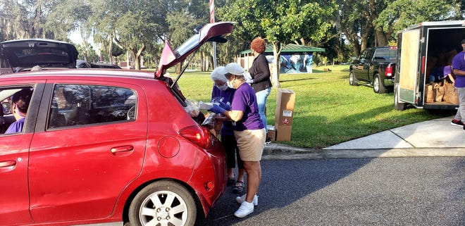 Marie Ficalora and Josephine Kasinger-Allman place some bread and a small box of pastries into the trunk of Lety Perez's car on Thursday, Nov. 19, 2020. The women were volunteering during a food giveaway by Backpack Buddies of Orange City, a nonprofit.