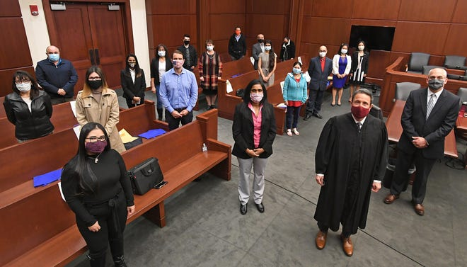 Hailing from 12 countries, 17 new U.S. citizens are shown Friday following a citizenship and naturalization ceremony at U.S. District Court in Erie. Presiding over the ceremony (shown at foreground, right) was U.S. Magistrate Judge Richard Lanzillo.