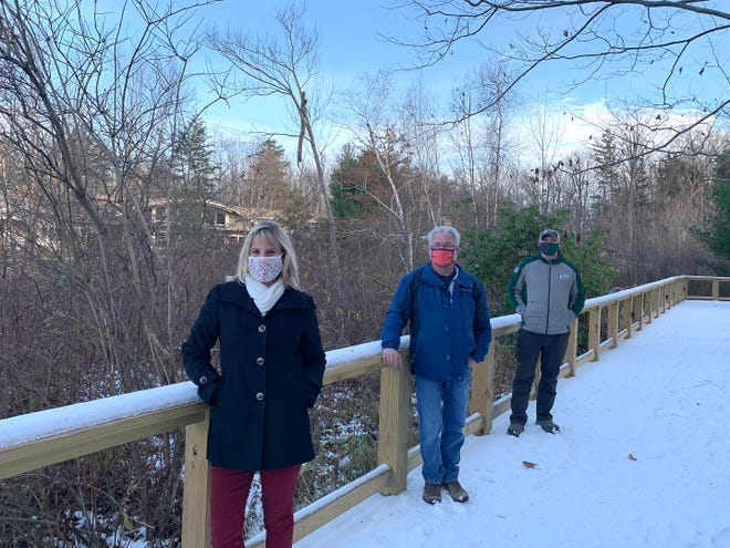 Jennifer Farrar, left, executive director of Asbury Woods, is shown on its boardwalk with Jason Earley, center, owner of Weiss Earley Landscape Design & Contracting, and Jake Thomas of J. Thomas Tree Service. Staff, supporters and sponsors are working to present a Winter Wonderland at Asbury Woods despite the coronavirus pandemic.