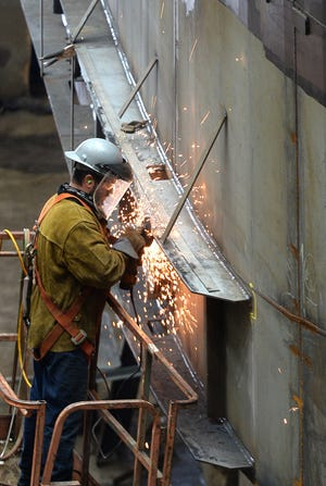 Steve Hart, a first class fitter at Donjon Shipbuilding & Repair works Friday on the J. Arnold Wittee, a new tugboat under construction at the facility.