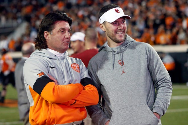 Oklahoma State coach Mike Gundy, left, talks with Oklahoma coach Lincoln Riley before their game last season. The Cowboys and Sooners meet in the annual Bedlam game this week with Big 12 Championship implications.