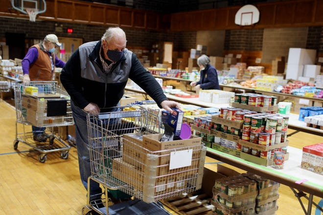 Volunteer Don Kuechmann, fills a grocery cart with food Tuesday at the St. Vincent de Paul food pantry for the Divine Mercy Parish at 700 Division Street in Burlington. Due to COVID-19 restrictions food bundles along with some toiletries are boxed and bag based on the number of residents in a home and then brought out and loaded into client's vehicles.