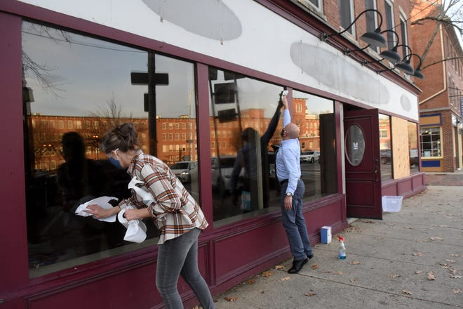Dover business owners Kim Clairmont of Cocheco Cafe and Doug Glennon of Jewelry Creations work with others to decorate the former Nicoles Hallmark as part of an effort to spruce up the downtown for Small Business Saturday and the holiday season.