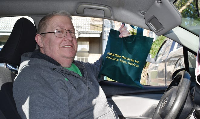 Fall River resident Richard Kelly picks up food at Bristol County Elder Services in Fall River on Wednesday.