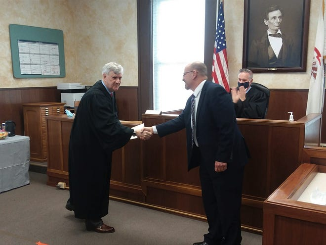 Marshall County State's Attorney Paul Bauer, right, is congratulated by retiring Judge Michael McCuskey after taking the oath as the county's new resident judge in the first of two ceremonies on Thursday. Seated at the bench is Chief Judge Paul Gilfillan of the Peoria-based 10th Judicial Circuit.