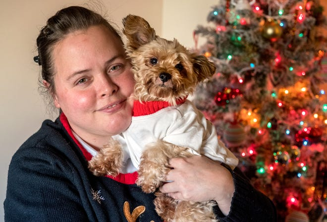Kimberley Krietemeyer cuddles her dog, Buttons, a female Yorkie/Chihuahua mix, in her Glen Oak Towers apartment in Peoria. Paralyzed and confined to a wheelchair, Krietemeyer only has the use of her left arm and is unable to work.