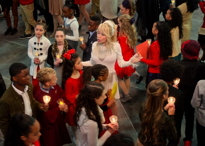 """This image released by Netflix shows Dolly Parton in a scene from """"Dolly Parton's Christmas on the Square."""""""