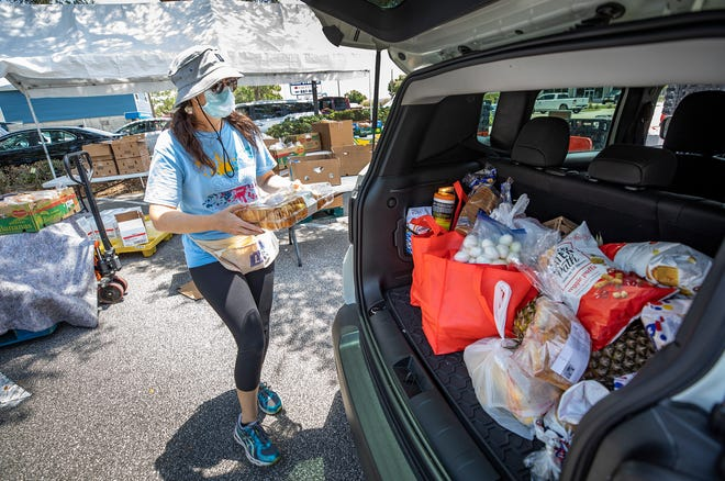 Summer Jenks loads food items into the back of cars lined up at the  Blessings & Hope Food Pantry in Lakeland. Neighbors rallying to the aid of their neighbors in need has been one of the blessings seen in Polk County during the pandemic.