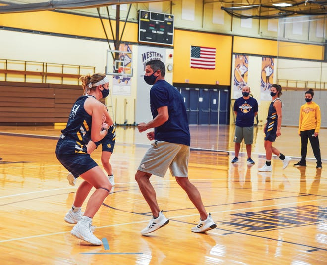 Western Illinois' Evan Zars sets a screen on coach JD Gravina during a practice from earlier this fall.
