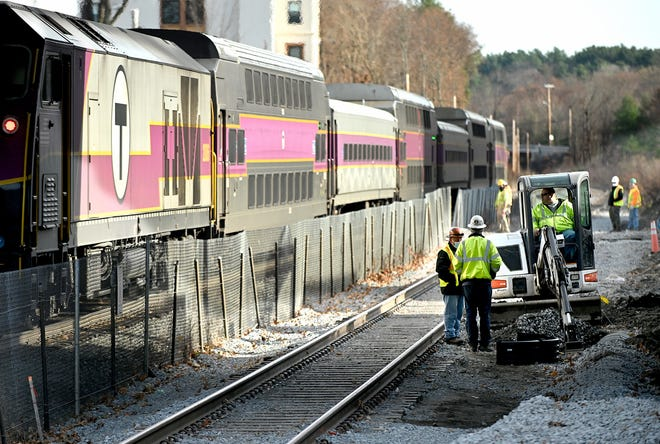 A commuter rail train passes as reconstruction continues at the Natick Center Station, Nov. 20, 2020.