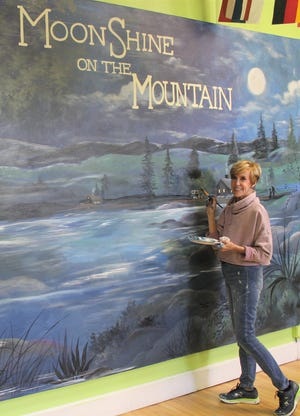 "Gale Hinton adds finishing touches to the mural for the Children's Museum Gala, with the theme ""MoonShine on the Mountain."""