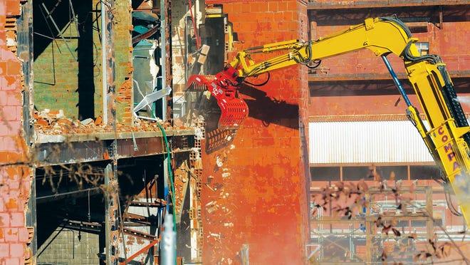 Environmental management crews begin knocking down the three-story 65,000-square-foot Building 9210 at Oak Ridge on Monday, Nov. 16.