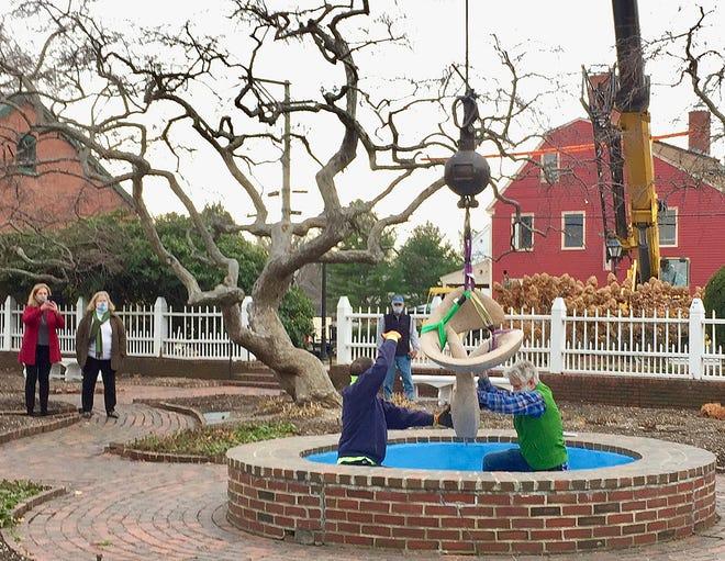"Sculptor Richard Erdman installs ""Odyssey"" in the center fountain of Prescott Park's formal gardens. Elizabeth Dinan photo"